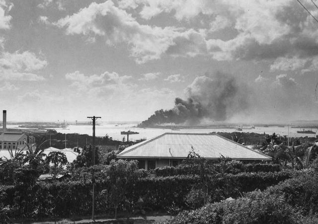 На заднем плане видна горящая и тонущая «Аризона» после налета японских бомбардировщиков 7 декабря 1941 года (ВМС США)