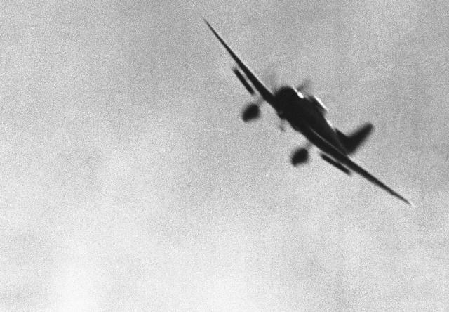 Японский пикирующий бомбардировщик на выходе из пике с выпущенными закрылками, снимок сделан фотографом ВМС США 7 декабря. (AP Photo)